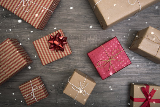 Christmas presents gift red and rustic decorated laid on wooden table background among snowing fall.
