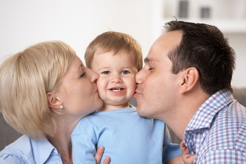 Father and mother kissing baby boy