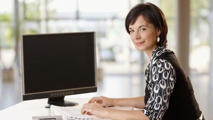 Happy businesswoman working at desk in office