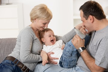 Happy caucasian couple playing with baby