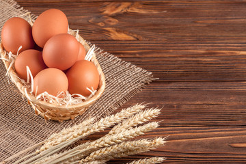 Chicken eggs horizontal banner. Eco farming concept. Red eggs and wheat ears on piece of sacking on brown wooden textured background. Organic food.