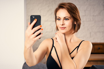 Pretty cute woman taking a selfie while sitting on a sofa at home