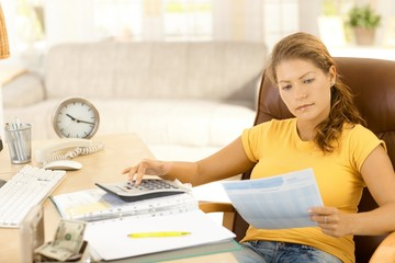 Young woman calculating expenses at home