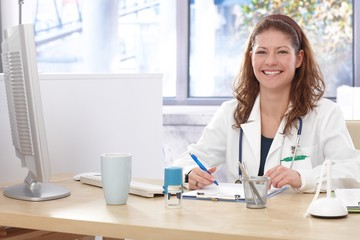 Female doctor sitting at desk smiling