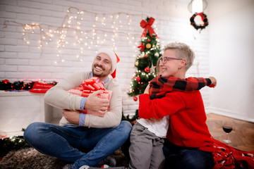Little kid hugging his short hair mother while sitting on a carpet near father with Santa hat and a big present for Christmas holidays at home.