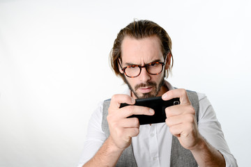 portrait of a 30 years old nerd geek playing game app on a smartphone isolated on white background