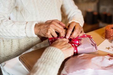 Unrecognizable senior couple in sweaters wrapping Christmas gift.