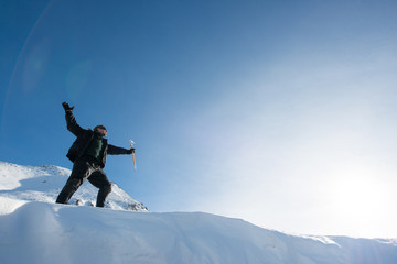 Happy climber with an ice ax in the snowy mountains