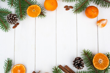 Christmas frame with Christmas tree branch and tangerine on a white wooden background