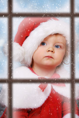 view through the window on cute baby girl in santa hat