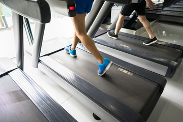 Gym treadmill closeup with man legs running. Concept for exercising, fitness and healthy lifestyle