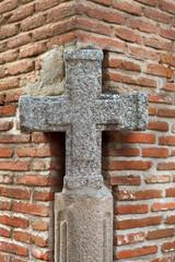 Grey stone cross in a corner