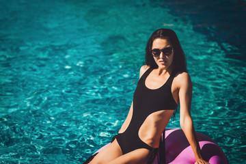 girl in black bikini on the inflatable ring in the swimming pool. Summer Vacation. Enjoying suntan. Weekend on resort