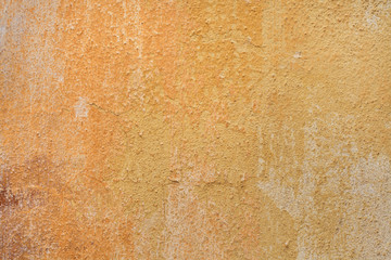 Yellow ochre painted stucco wall. Background texture