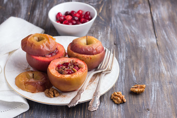 Baked apples stuffed with cranberries, walnuts and honey with cinnamon on a white plate on a wooden table, selective focus. Delicious healthy vegan dessert