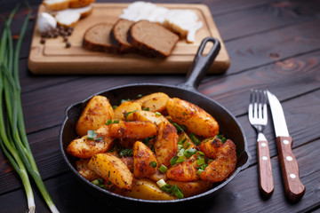 Roasted potatoes, bacon, rye bread and scallion on dark wooden table. Appetizing countryside homemade traditional food.