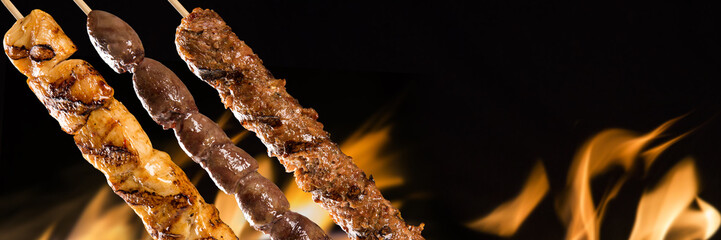 Assorted steak skewers on a fire background