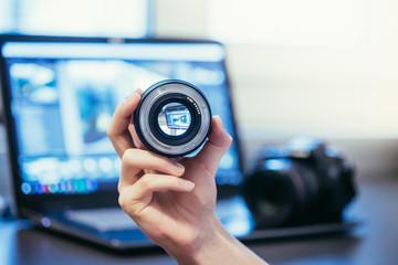 Objektiv wird in der Hand gehalten, Laptop im und Spiegelreflex Kamera im Hintergrund