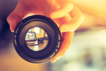 Kamera-Objektiv wird in der Hand gehalten, Laptop und Kamera im 'Sucher'