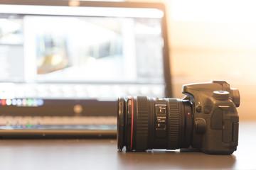 Profi Spiegelreflexkamera auf dem Tisch, Laptop im Hintergrund