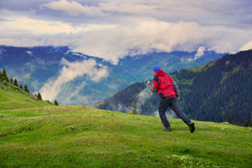 Traveler runs through the green alpine meadow