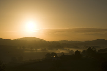 Bright golden sunrise over the hills and fields with early morning mist in the valleys in the Herefordshire countryside, England