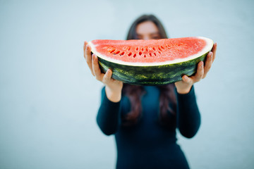 Woman holding watermelon in hands