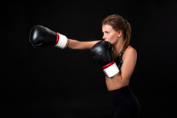 Beautiful female athlete in boxing gloves, in the studio on a black background.
