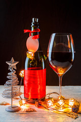 New Year's photo of bottle with red ribbon, Christmas tree toys, wine glass
