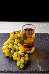 Photo of glass with juice, bunch of grapes on stone board