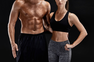 Sport, fitness, workout concept. Fit couple, strong muscular man and slim woman posing on a black background