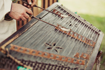 Ukrainian traditional music string instrument tsymbaly. Man wearing traditional clothes playing folk Ukrainian music. Close view.