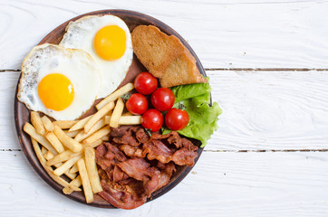 Breackfast : french fries , bacon and fried eggs