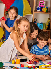 Small students with teacher finger painting in art school class. Mom and kids at home. Craft drawing education develops creative abilities of children. Drawing courses for children.
