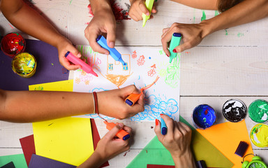 Hands hold colorful markers and draw kids illustration