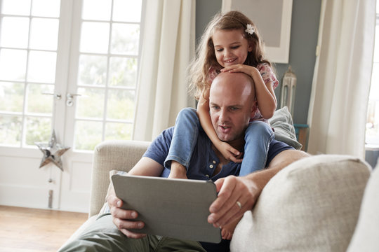 Father using digital tablet while daughter sitting on his shoulder at home