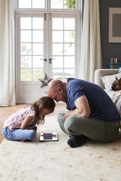 Father and daughter using digital tablet while sitting on floor at home