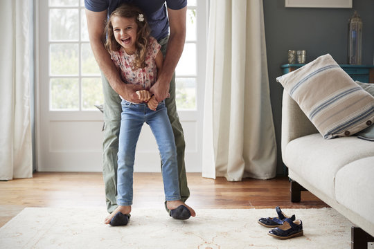 Portrait of smiling girl balancing on father's feet at home