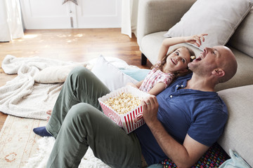 Girl feeding dad popcorn while watching TV together at home