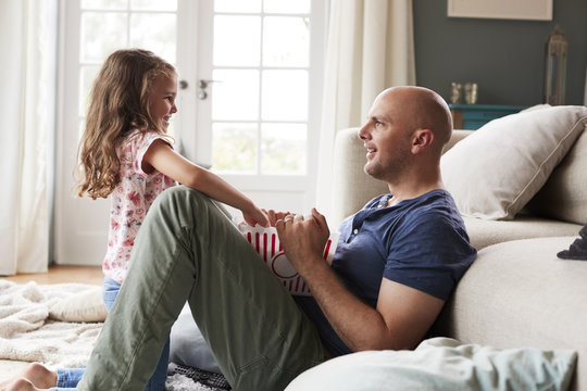 Side view of smiling father and daughter eating popcorn at home
