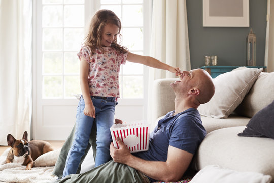 Daughter feeding popcorn to father at home