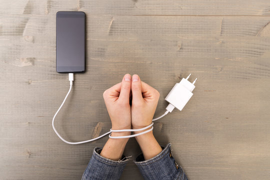 Female hands and smartphone. Woman's hands trapped and wrapped on wrists with mobile phone cable as handcuffs. Addiction to internet and social networks