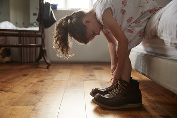 Girl sitting on bed and trying on dad's boots at home