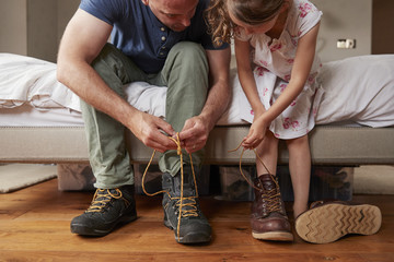 Dad teaching his daughter how to tie shoelaces, front view