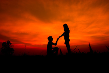 silhouette of a romantic couple on beauty sunset. A man kneels kissing a girlfriend's hand.