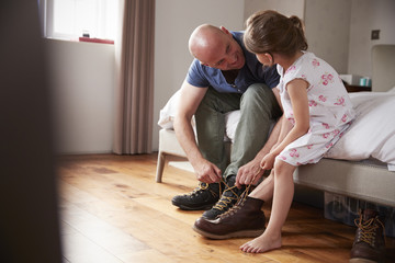 Dad teaching his daughter how to tie shoelaces, side view