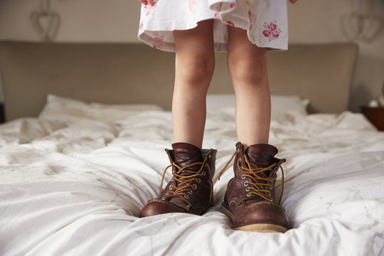 Child wearing adult boots on bed
