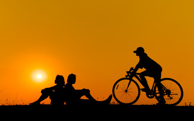 silhouette of young woman cyclist and jumping on sunset sky with stop on the prairie at yellow evening horizon sea yellow sunset heaven background Outdoor.