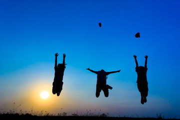 silhouette of children jumping on the prairie at yellow evening horizon sea yellow sunset heaven background outdoor.