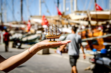 A small souvenir ship on the background of large ships on the Bodrum embankment in the hand of a tourist.
